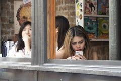 Κορίτσια που κάθονται στον καφέ δολοφόνων δημητριακών στην πάροδο τούβλου, δημοφιλής θέση hipster Στοκ Εικόνες