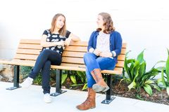 Κορίτσια που κάθονται στον πάγκο από κοινού Στοκ Εικόνες