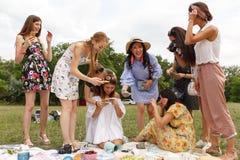 Κορίτσια που κάνουν τα phtos του επιπέδου να βάλουν τη διακόσμηση του κόμματος πικ-νίκ στοκ φωτογραφία