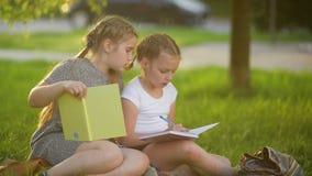 Κορίτσια που κάνουν την εργασία στο θερινό κήπο Έχουν πολλή διασκέδαση που παίρνει τη γνώση απόθεμα βίντεο