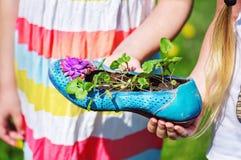 Κορίτσια που κρατούν ένα παλαιό, διακοσμημένο και χρωματισμένο θηλυκό παπούτσι με το α Στοκ Εικόνα