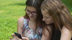 Κορίτσια που ξοδεύουν τον ελεύθερο χρόνο με το κινητό τηλέφωνο απόθεμα βίντεο