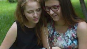 Κορίτσια που ξοδεύουν το χρόνο με το κινητό τηλέφωνο υπαίθριο απόθεμα βίντεο