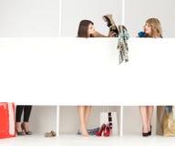 Κορίτσια που δοκιμάζουν το κατάστημα ενδυμάτων wordrobe Στοκ φωτογραφία με δικαίωμα ελεύθερης χρήσης