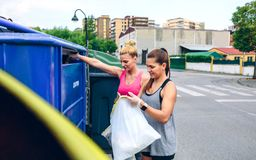 Κορίτσια που ρίχνουν τα απορρίματα στην ανακύκλωση dumpster στοκ εικόνες με δικαίωμα ελεύθερης χρήσης