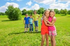 Κορίτσια που στέκονται στο αγκάλιασμα πάρκων στοκ φωτογραφίες