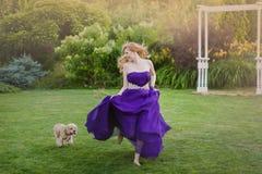 Κορίτσια που τρέχουν στο lown με το σκυλί Στοκ φωτογραφία με δικαίωμα ελεύθερης χρήσης