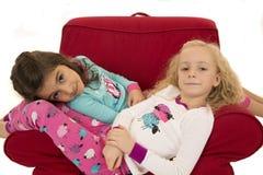 Κορίτσια που φορούν τις χειμερινές πυτζάμες που κάθονται σε μια κόκκινη καρέκλα στοκ εικόνες με δικαίωμα ελεύθερης χρήσης
