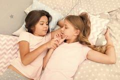 Κορίτσια που χαλαρώνουν στο κρεβάτι Slumber έννοια κομμάτων Τα κορίτσια θέλουν ακριβώς να έχουν τη διασκέδαση Προσκαλέστε το φίλο στοκ φωτογραφία με δικαίωμα ελεύθερης χρήσης