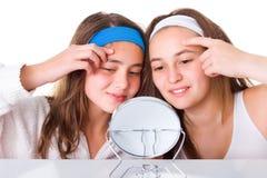 Κορίτσια που ψάχνουν για blemishes σε δικοί τους το δέρμα Στοκ Εικόνες