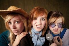 κορίτσια προσώπων που κατασκευάζουν το μικρόφωνο τρεις νεολαίες Στοκ Φωτογραφία