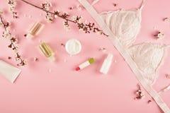Κορίτσια πρωινού έννοιας Στηθόδεσμος, προϊόντα φροντίδας δέρματος και ανθίζοντας κλάδος σε ένα ρόδινο υπόβαθρο r στοκ φωτογραφίες