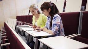 Κορίτσια σπουδαστών με τα σημειωματάρια στην αίθουσα διάλεξης απόθεμα βίντεο