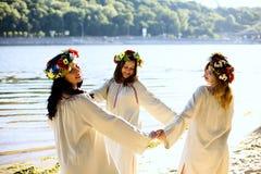 Κορίτσια στα εθνικά ενδύματα με το στεφάνι του εορτασμού λουλουδιών Στοκ Εικόνα
