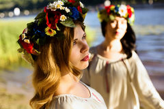 Κορίτσια στα εθνικά ενδύματα με το στεφάνι του εορτασμού λουλουδιών Στοκ Φωτογραφία