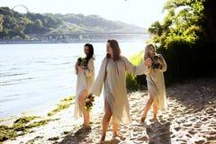 Κορίτσια στα εθνικά ενδύματα με το στεφάνι του εορτασμού λουλουδιών Στοκ Φωτογραφίες