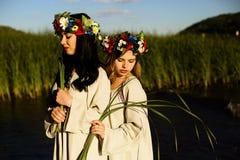 Κορίτσια στα εθνικά ενδύματα με το στεφάνι του εορτασμού λουλουδιών Στοκ Εικόνες