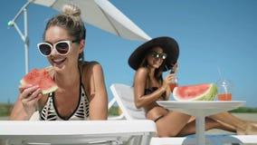 Κορίτσια στην παραλία, που χαμογελά και που γελά, τρώγοντας το καρπούζι, που βρίσκεται στο μόνιππο longue απόθεμα βίντεο