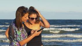 Κορίτσια στην παραλία που έχει έναν καταπληκτικό χρόνο κουβεντιάζοντας στα κοινωνικά μέσα απόθεμα βίντεο