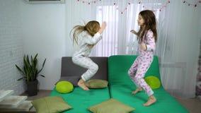 Κορίτσια στις πυτζάμες που χορεύουν στον καναπέ απόθεμα βίντεο