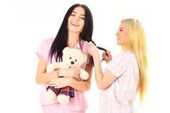 Κορίτσια στις ρόδινες πυτζάμες, απομονωμένο άσπρο υπόβαθρο Οι κυρίες στα πρόσωπα χαμόγελου με το παιχνίδι βελούδου αντέχουν το βλ Στοκ εικόνα με δικαίωμα ελεύθερης χρήσης