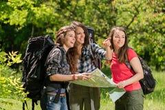 Κορίτσια τουριστών στο δάσος με το χάρτη και τα σακίδια πλάτης στοκ εικόνες