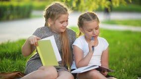 Κορίτσια Cutie που κάνουν την εργασία μαζί υπαίθρια Παίρνουν το afterschool γνώσης απόθεμα βίντεο