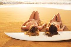 Κορίτσια Surfer στην παραλία στο ηλιοβασίλεμα στη Χαβάη Στοκ Εικόνα