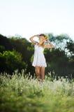 Κορίτσι άσπρα sundress και ένα στεφάνι των λουλουδιών στο επικεφαλής aga της Στοκ φωτογραφία με δικαίωμα ελεύθερης χρήσης