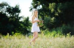 Κορίτσι άσπρα sundress και με ένα στεφάνι των λουλουδιών υπό εξέταση επάνω Στοκ Φωτογραφία