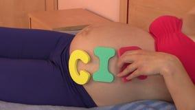 Κορίτσι λέξης επιλογών εγκύων γυναικών από τις επιστολές παιχνιδιών στο στομάχι της απόθεμα βίντεο