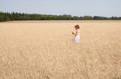 Κορίτσι 4 έτη σε έναν τομέα βρωμών Στοκ Εικόνες