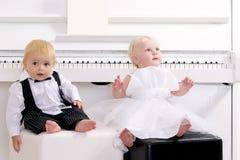 κορίτσι αγοριών κοντά στη συνεδρίαση πιάνων στοκ εικόνες