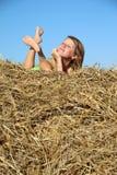 Κορίτσι αγροτών που στηρίζεται στη θυμωνιά χόρτου στοκ φωτογραφίες με δικαίωμα ελεύθερης χρήσης