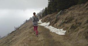 Κορίτσι αθλητών που τρέχει μέσω της χιονώδους πορείας ιχνών πίσω από την ακολουθία Πραγματική αθλητική κατάρτιση δρομέων γυναικών απόθεμα βίντεο