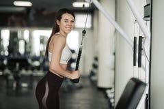 Κορίτσι αθλητών sportswear που επιλύει και που εκπαιδεύει τα όπλα και τους ώμους της με τη μηχανή άσκησης στη γυμναστική στοκ φωτογραφία με δικαίωμα ελεύθερης χρήσης