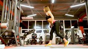 Κορίτσι αθλητών sportswear που επιλύει και που εκπαιδεύει τη γυμναστική της όπλων και ώμων φιλμ μικρού μήκους