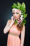 Κορίτσι ανοίξεων ομορφιάς με την τρίχα λουλουδιών Όμορφη πρότυπη γυναίκα με τα λουλούδια στο κεφάλι της Η φύση Hairstyle Καλοκαίρ Στοκ Εικόνες