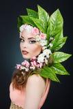 Κορίτσι ανοίξεων ομορφιάς με την τρίχα λουλουδιών Όμορφη πρότυπη γυναίκα με τα λουλούδια στο κεφάλι της Η φύση Hairstyle Καλοκαίρ Στοκ Εικόνα