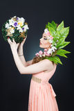 Κορίτσι ανοίξεων ομορφιάς με την τρίχα λουλουδιών Όμορφη πρότυπη γυναίκα με τα λουλούδια στο κεφάλι της Η φύση Hairstyle Καλοκαίρ Στοκ φωτογραφία με δικαίωμα ελεύθερης χρήσης