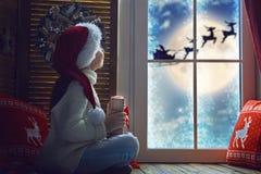 Κορίτσι από το παράθυρο στα Χριστούγεννα Στοκ Εικόνες