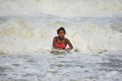 Κορίτσι αφροαμερικάνων που κολυμπά στα ωκεάνια κύματα στοκ φωτογραφίες