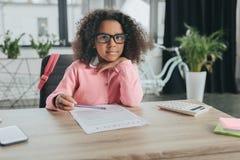 Κορίτσι αφροαμερικάνων που προσποιείται να είναι επιχειρηματίας και που κάνει τη γραφική εργασία στην αρχή Στοκ Φωτογραφία