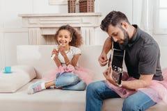 Κορίτσι αφροαμερικάνων που τραγουδά ενώ κιθάρα παιχνιδιού πατέρων στο σπίτι Στοκ φωτογραφίες με δικαίωμα ελεύθερης χρήσης