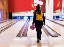 Κορίτσι για να κυλήσει περίπου μια έννοια χόμπι και ελεύθερου χρόνου σφαιρών μπόουλινγκ Στοκ Φωτογραφίες