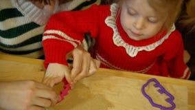 Κορίτσι γυναικών και μικρών παιδιών που προετοιμάζει το μελόψωμο για το γεύμα οικογενειακής Παραμονής Χριστουγέννων φιλμ μικρού μήκους