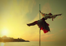 Κορίτσι γυναικών στο χορό πόλων άσκησης φορεμάτων ενάντια στη θάλασσα ηλιοβασιλέματος. Στοκ Φωτογραφία