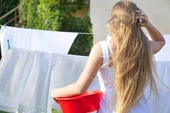 Κορίτσι εφήβων με μια πλαστική λεκάνη Ξεραίνοντας το καθαρό πλυντήριο στο σχοινί υπαίθρια την ηλιόλουστη ημέρα στοκ φωτογραφίες