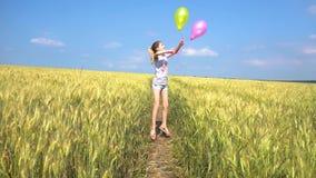Κορίτσι εφήβων με τα μπαλόνια που πηδά στον τομέα φιλμ μικρού μήκους