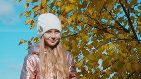 Κορίτσι εφήβων πορτρέτου το φθινόπωρο ΚΑΠ και παλτό στο κίτρινο υπόβαθρο φυλλώματος απόθεμα βίντεο